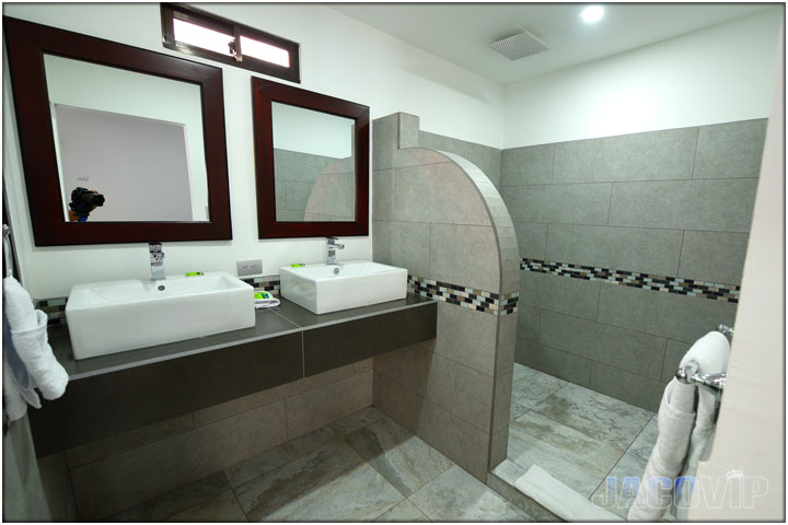 Bathroom with 2 sinks and rounded shower seperation